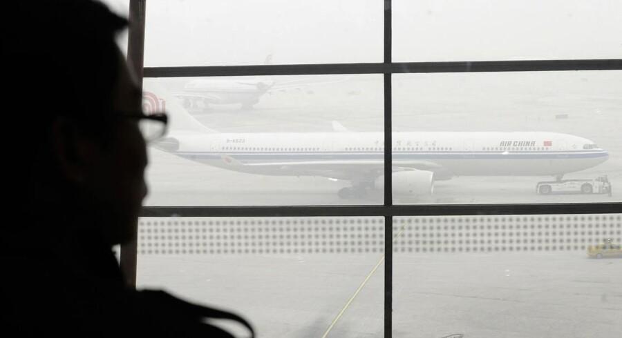 En rejsende kigger ud på flyene en tåget dag i Beijing International Airport. Opgørelse viser, at det står skidt til med præcisionen i den kinesiske lufthavn.