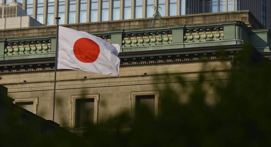 Et japansk flag foran Bank of Japans hovedsæde i Tokyo
