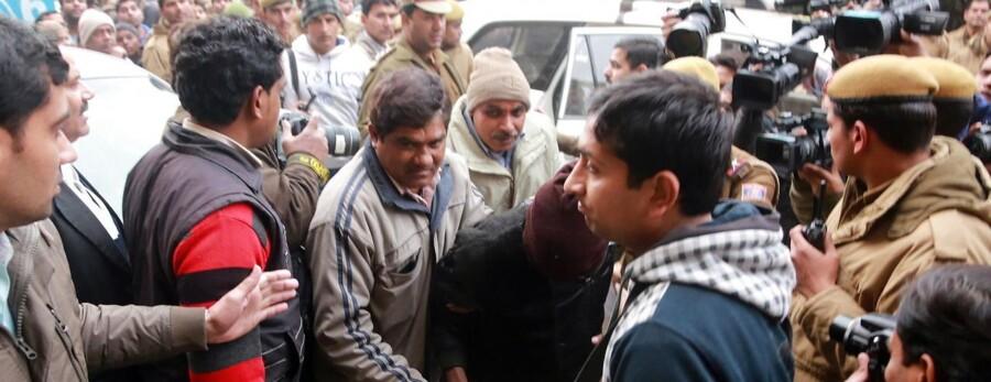 Indiske politifolk eskorterer en af de anklagede mænd (med hoved dækket) til Retten i New Dehli 16. januar.