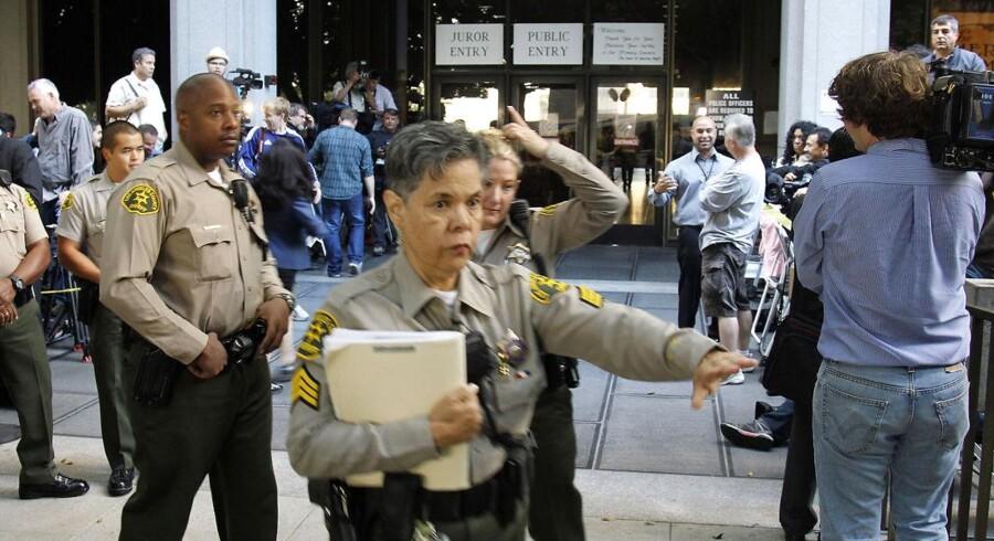 Vicesheriffer holder journalister og tilskuere på afstand inden retssagen går i gang i Los Angeles.