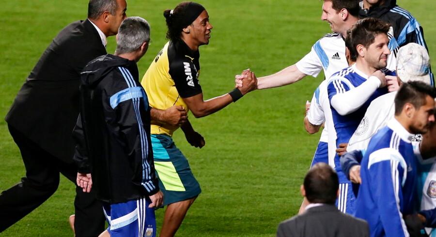 Ronaldinho er ikke med til VM for Brasilien, men til Argentinas træning onsdag fik fodbold-verdenen alligevel en slags fornemmelse af, hvordan et møde mellem ham og Lionel Messi kunne have set ud anno 2014.Flere fans stormede banen under Argentinas træning i Belo Horizonte, og blandt dem var en mand med en vis lighed med Ronaldinho. Måske er det også derfor, at Messi smiler så bredt over mødet.Det kan selvfølgelig også være, at det blot er generel optimisme, der præger den argentinske superstjerne, for sammen med sine holdkammerater er han kommet i en af VM's blødere pulje. I indledende gruppespil venter Bosnien, Nigeria og Iran på argentinerne.