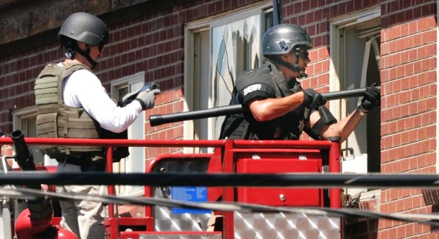 Betjente stikker et kamera på en stang ind i den formodede gerningsmands minerede lejlighed for at orientere sig.