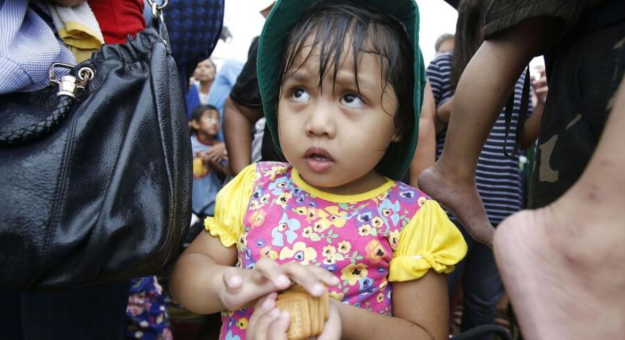 En lille pige kigger op efter at have modtaget kiks fra FN.
