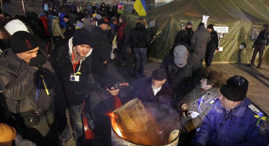 Onsdag aften forsøgte deltagerne i demonstrationerne for EU i Ukraines hovedstad, Kiev, at holde sig varme.