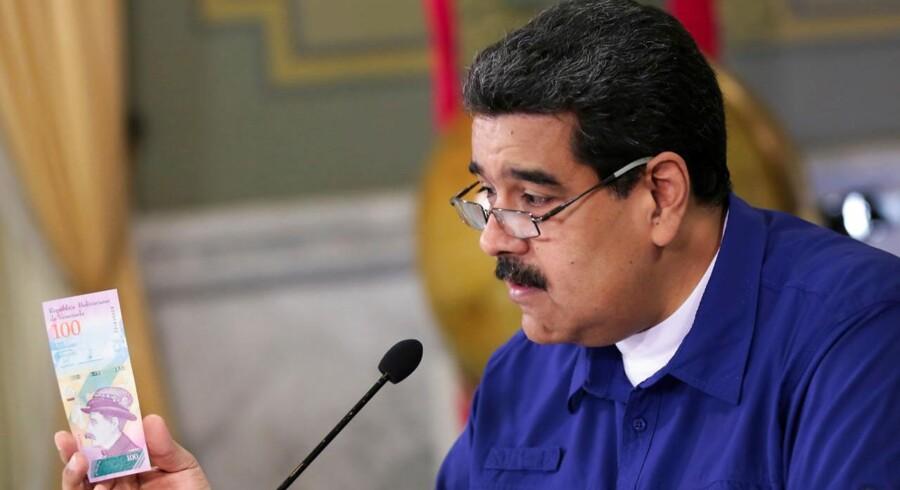 Venezuela's præsident Nicolas Maduro holder en af landets nye pengesedler i hånden.