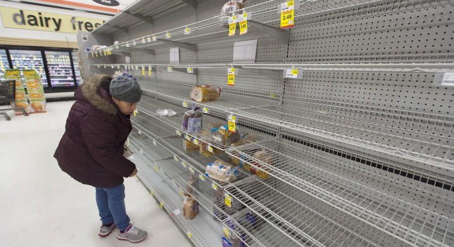 En kunde har ikke meget at vælge mellem i brødsektionen i et amerikansk supermarked, hvor folk er strømmet til for at forberede sig på en kommende snestorm.