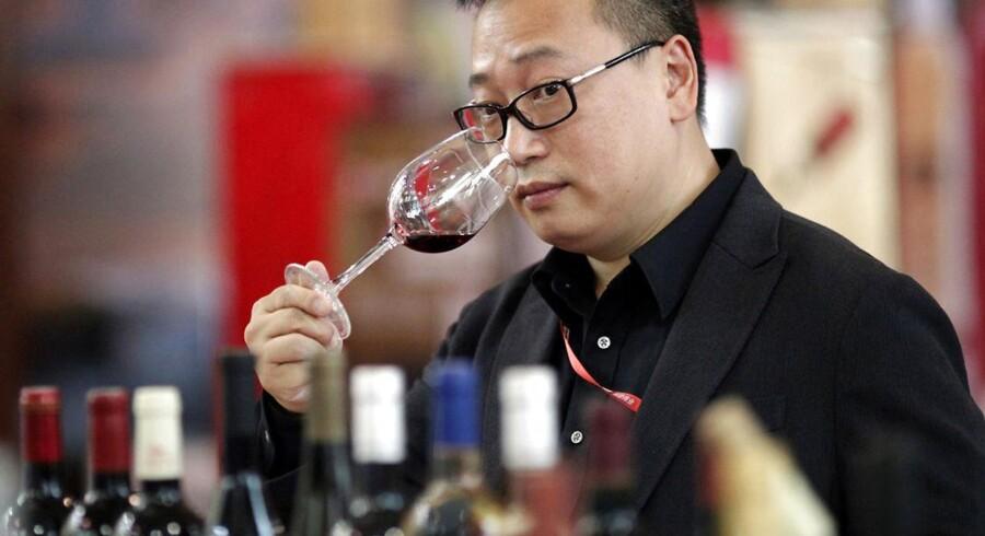 Kina har i dag verdens femtestørste forbrug af vin. Og interessen for dyre dråber er stigende. Her ses en deltager til en international vinmesse i Shanghai i juni.