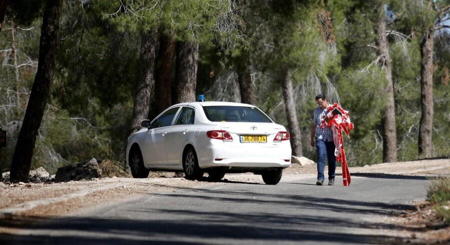 En politimand nær stedet i en skov, hvor en palæstinensisk teenager blev fundet dræbt nær Jerusalem.