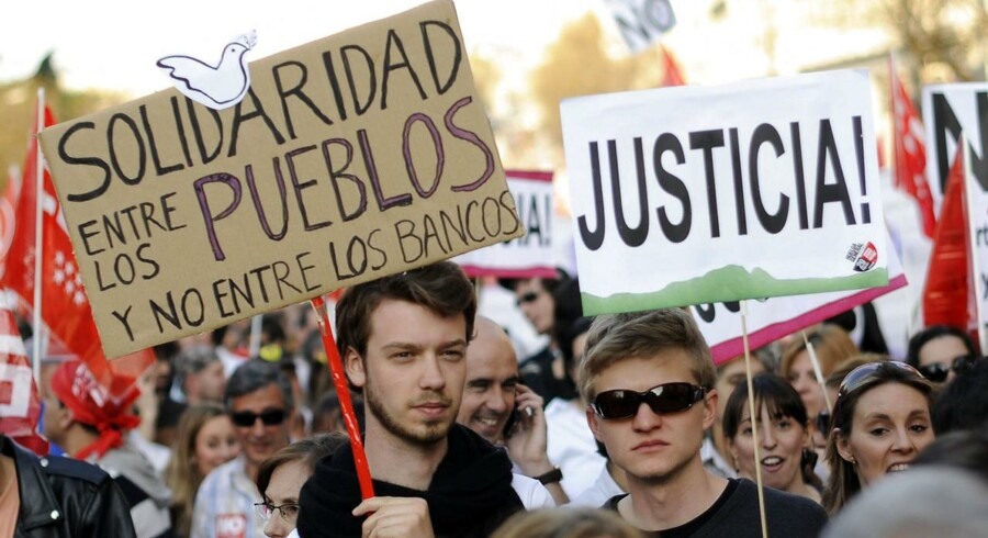 """""""Solidaritet mellem mennesker og ikke mellem bankerne"""" står der på skiltet under en demontration i Madrid i slutningen marts. De spanske banker er i krise efter at have lånt ud under boligboblen."""