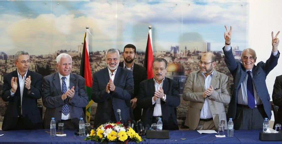 Senior Fatah official Azzam Al-Ahmed (2nd L), head of the Hamas government Ismail Haniyeh (3rd L) and senior Hamas leader Moussa Abu Marzouq (2nd R) clap after announcing a reconciliation agreement in Gaza City April 23, 2014. The Gaza-based Islamist group Hamas and President Mahmoud Abbas's Palestine Liberation Organization (PLO) agreed on Wednesday to implement a unity pact, both sides announced in a joint news conference.REUTERS/Suhaib Salem (GAZA - Tags: MILITARY POLITICS)