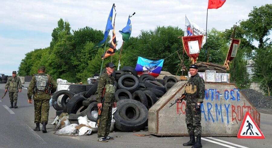 Pro-russiske separatister står vagt ved en vej mellem Luhansk og Donetsk i det østlige Ukraine. De separatistiske grupper har indført natligt udgangsforbud og rationering af vand i storbyen med over 900.000 indbyggere. Det har ramt tusindvis af civile.