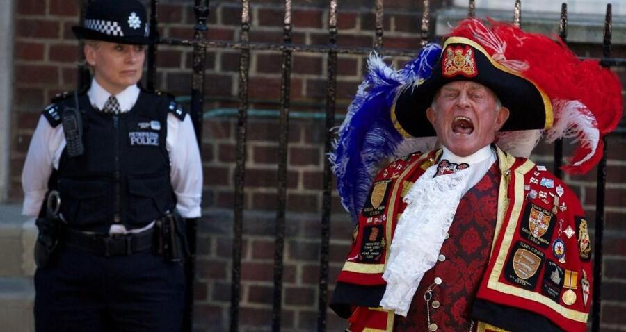"""En såkaldt """"Town Crier"""" råber annonceringen af den kongelige fødsel ud foran St. Mary's Hospital."""