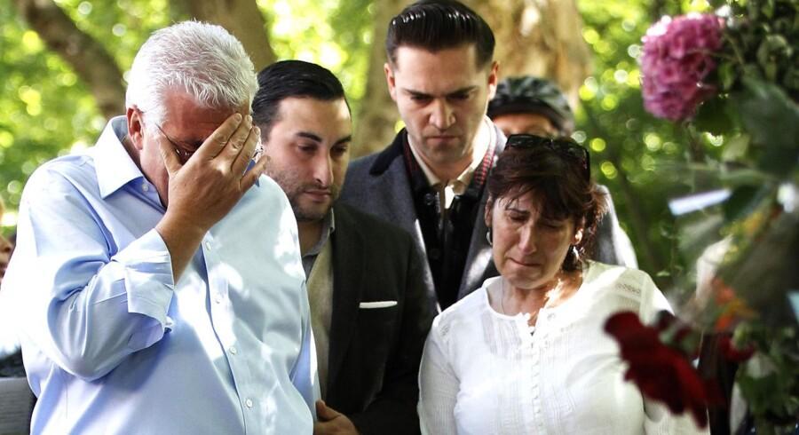 Amy Winehouses forældre står berørte og kigger på de mange blomster, fans har lagt ved deres afdøde datters hjem i London.