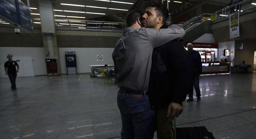 David Miranda, der har medvirket til offentliggørelsen af Edward Snowdens afsløringer af USA og Storbritanniens hemmelige overvågninger, blev tilbageholdt og udspurgt i ni timer, da han mellemlandede i Heathrow Lufthavn i London. Nu skal det undersøges, om myndighederne gik for vidt. Her modtages han med kram af Glenn Greenwald. Foto: Ricardo Moraes/Reuters