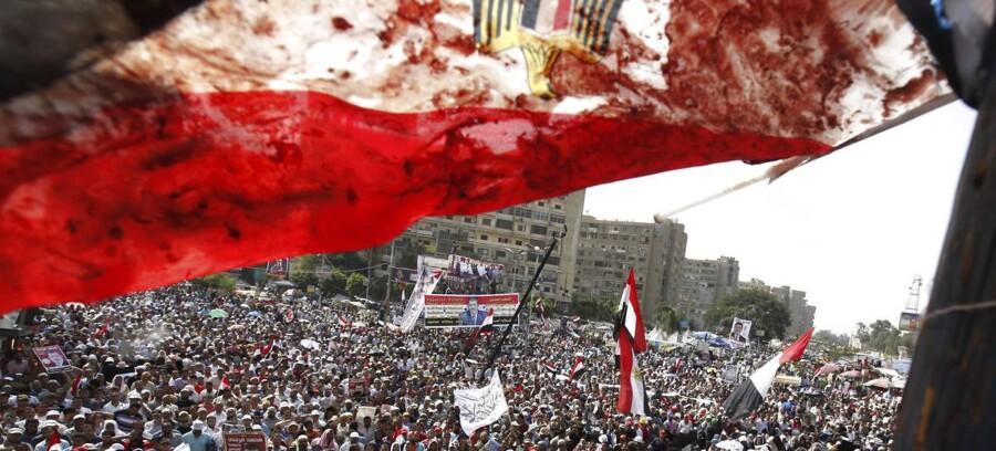 Kampene i Egypten mandag mellem Moris-tilhængere og militæret endte med mindst 42 dræbte og flere sårede. Her vejrer et blodplettet egyptisk flag over demonstranterne.
