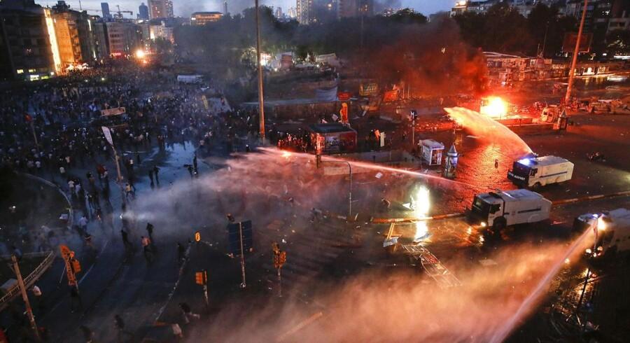 Demonstranter løber væk i panik, mens politi bruger vandkanoner og og tåregas til at sprede demonstranterne.
