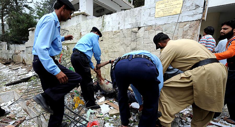 Pakistanske politifolk fjerner et lig foran den danske ambassade i Islamabad.