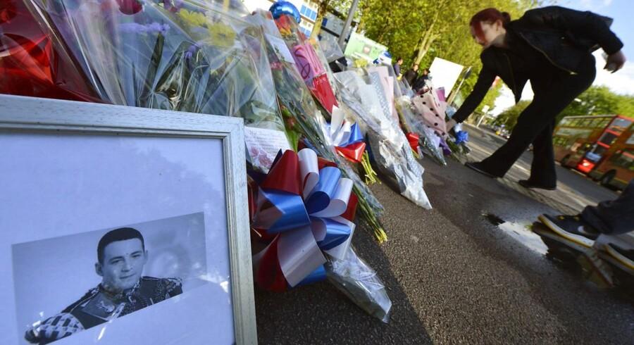 Folk lægger blomster ved billedet af den unge soldat Lee Rigby på det sted i London-forstaden Woolwich, hvor han blev dræbt i onsdags.