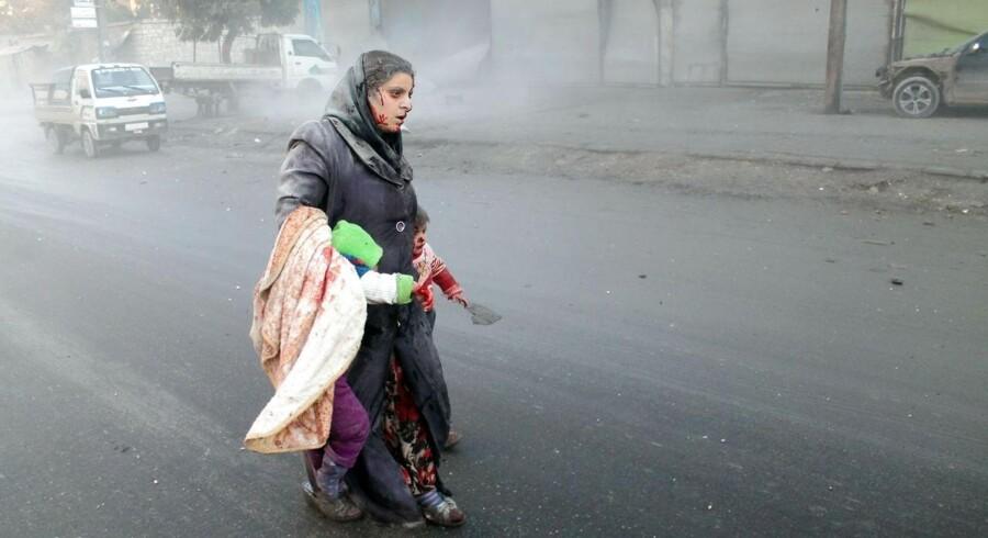 En såret kvinde bærer går med sine børn gennem de krigshærgede gader i Aleppo. Efter tre års borgerkrig er det en kamp alene at finde mad for syrerne.