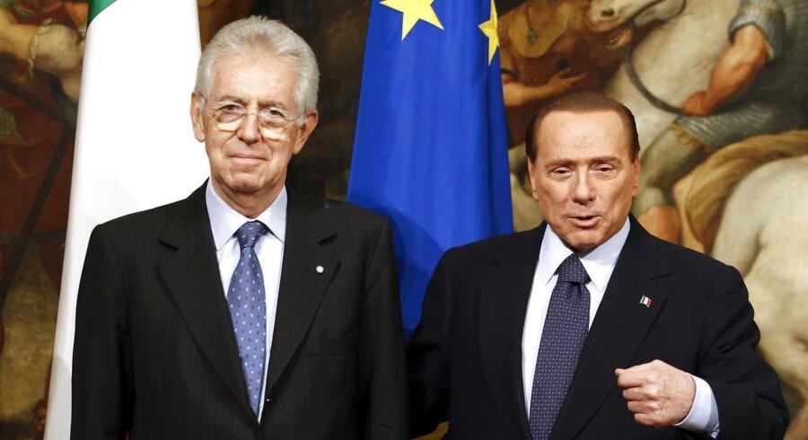 Premierminister Mario Monti (tv.) poserer her med Silvio Berlusconi i Chigi Paladset i Rom tilbage i november 2011. Nu vil Berlusconi tilbage i italiensk politik og lægger hårdt ud med at håne Monti.