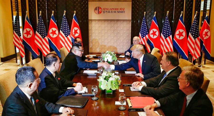 epa06801416 US President Donald J. Trump (3-R) and North Korean leader Kim Jong-un (3-L) shake hands across the table during the expanded bilateral meeting as part of the historic summit at the Capella Hotel on Sentosa Island, Singapore, 12 June 2018. The summit marks the first meeting between an incumbent US President and a North Korean leader. EPA/KEVIN LIM / THE STRAITS TIMES / SPH EDITORIAL USE ONLY