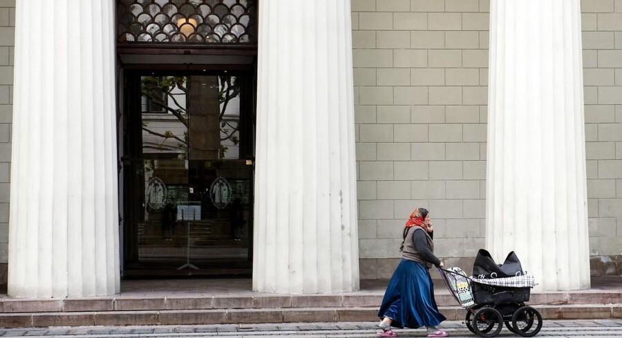 En hjemløs østeuropæer går forbi Vor Frue Kirke i det indre København.
