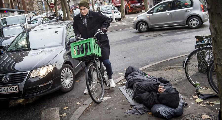 Midt i morgentrafikken ligger en hjemløs og sover på varmrist på Borgergade København.