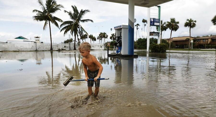 En dreng hjælper med oprydningen efter hans families benzinstation ved Everglades City i Florida oversvømmede ved orkanen Irma.