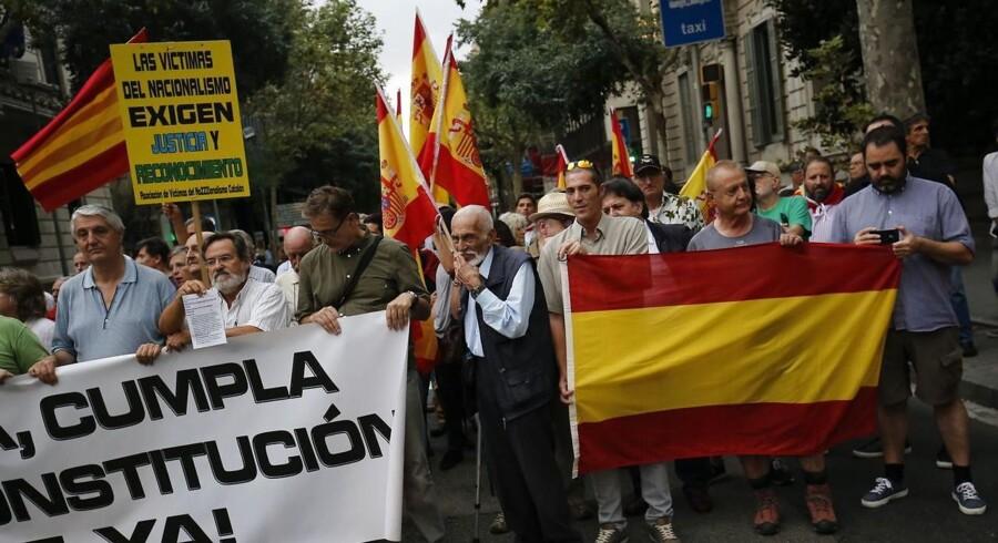 RB PLUS Barcelona og Madrid er på kollisionskurs- - Folk med spanske flag og et banner under en demonstration arrangeret af den spanske højreparti Vox foran Spaniens regeringsdelegation i Barcelona den 6. september 2017.- - Se RB UDLAND 08.15. En dyb politisk krise er brudt ud i Spanien, efter at selvstyreparlamentet i Catalonien har besluttet, at Cataloniens vælgere skal stemme om selvstændighed.. (Foto: PAU BARRENA/Scanpix 2017)