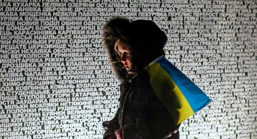 En pige står ved et monument med navnene på de steder i Ukraine, hvor mennesker sultede til døde. 2014.