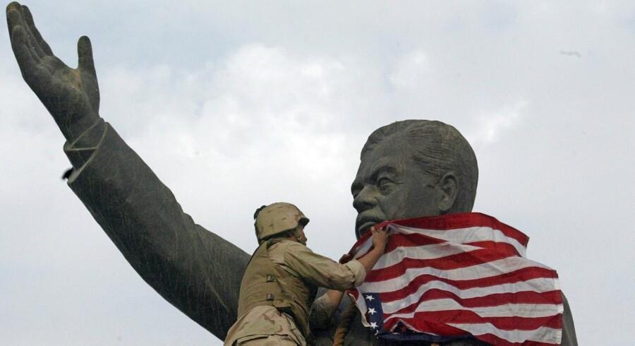 En amerikansk soldat dækker i 2003 en statue af Saddam Hussein med Stars & Stripes. Arkivfoto