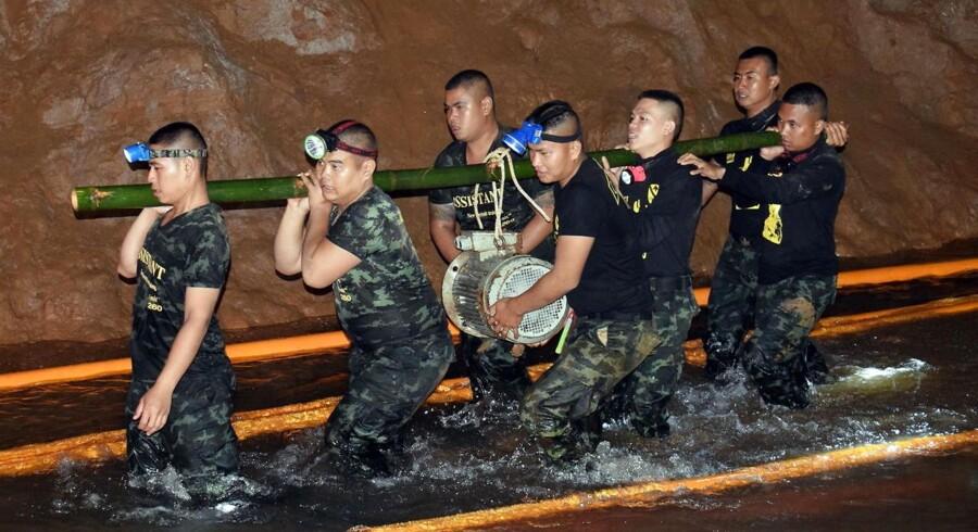 Thailandske soldater bærer udstyr i det oversvømmede hulsesystem, hvor 12 drengefodboldspillere og deres træner har siddet indespærret i snart 14 dage.