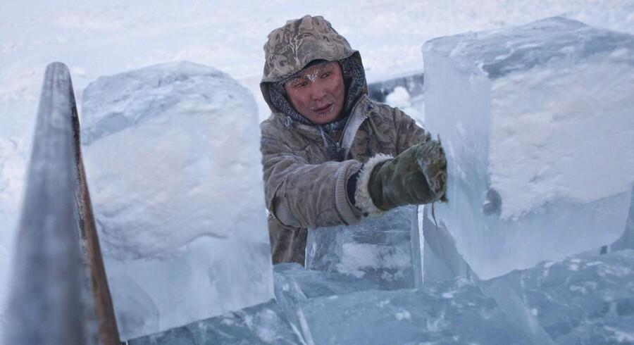 Store isblokke bliver løftet op på ladet af en lastbil nær sibiriske Jakutsk, verdens vinterkoldeste by på over 100.000 indbyggere.
