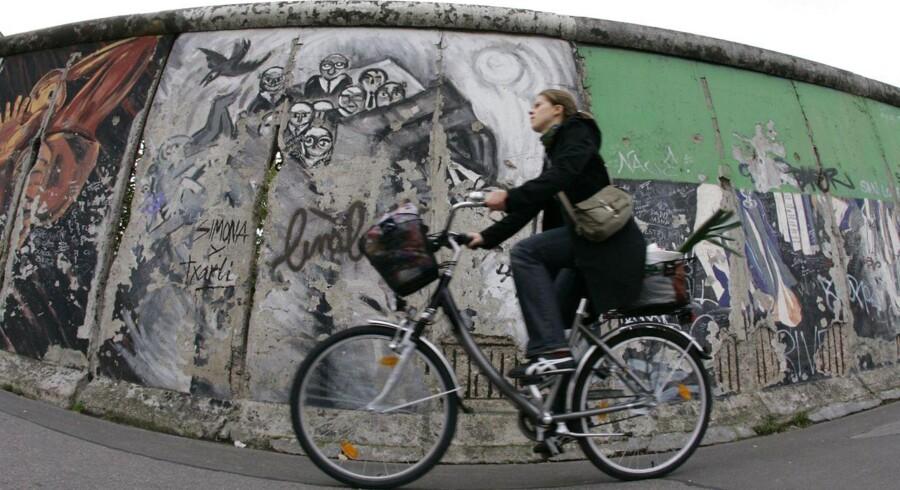En kvinde cykler forbi en rest af Berlin-muren.