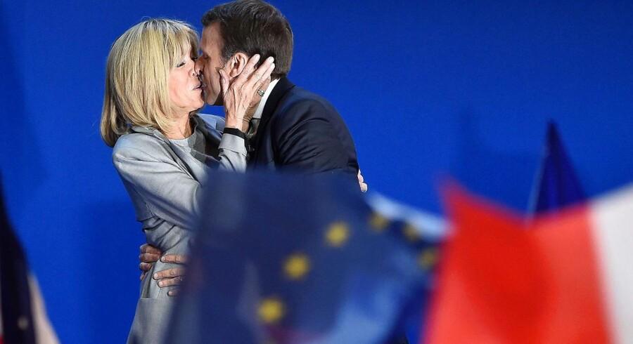 Brigitte Macron kysser sin mand på scenen før hans tale efter sejren i første valgrunde. Historien om det måske kommende præsidentpar i Frankrig er med Emmanuel Macrons egne ord »anderledes«, endda »aparte«.
