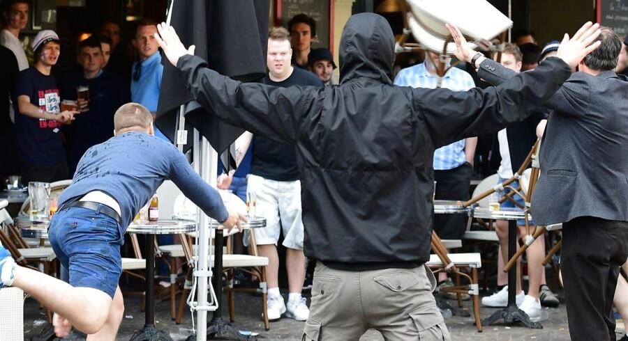 En russisk bølle smider en stol efter engelske fans på en café i den nordfranske by Lille. Nu kan Rusland være på vej ud af EM.