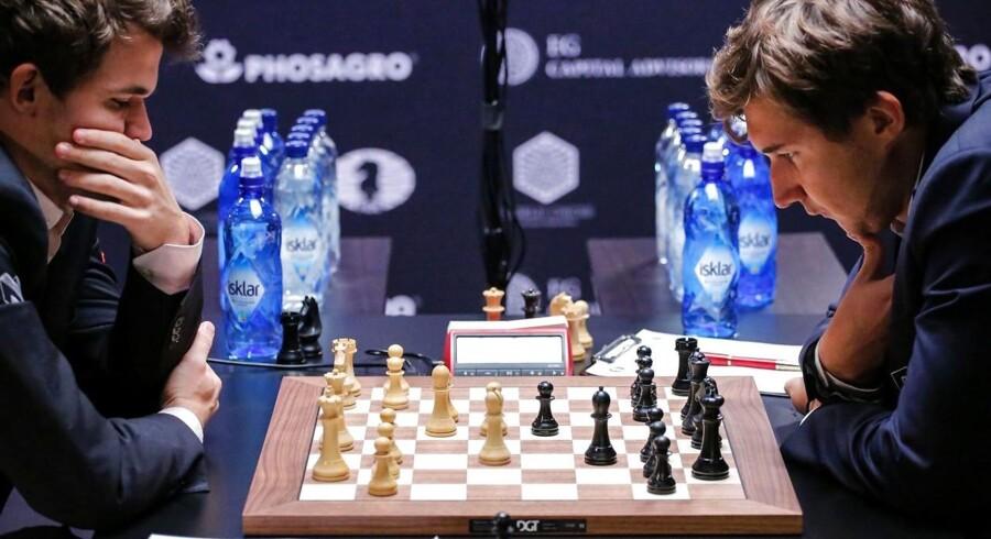 Nordmanden Magnus Carlsen (t.v.) og russeren Sergej Karjakin i dybe tanker under 12. parti af VM-turneringen i New York.