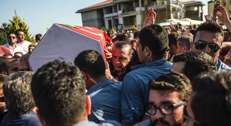 Tyrkiet præsident, Recep Tayyip Erdogan, (i midten af fotoet) er med til at bære kisten med et af ofrene for kupforsøget natten til lørdag. Erdogan sagde i sin tale ved begravelsen bl.a., at »vi vil fortsætte med at rense alle statslige institutioner for denne virus. For denne virus har desværre spredt sig som kræft. Foto: Bulent Kilic/AFP