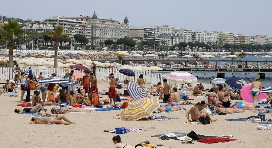 Cannes ved Cote d'Azur. Strandpromenaden La Croisette. Solbadende turister ved den offentlige strand nær Palais des Festivals. I baggrunden ses bla. Carlton Hotel (med de 2 sorte tårne).
