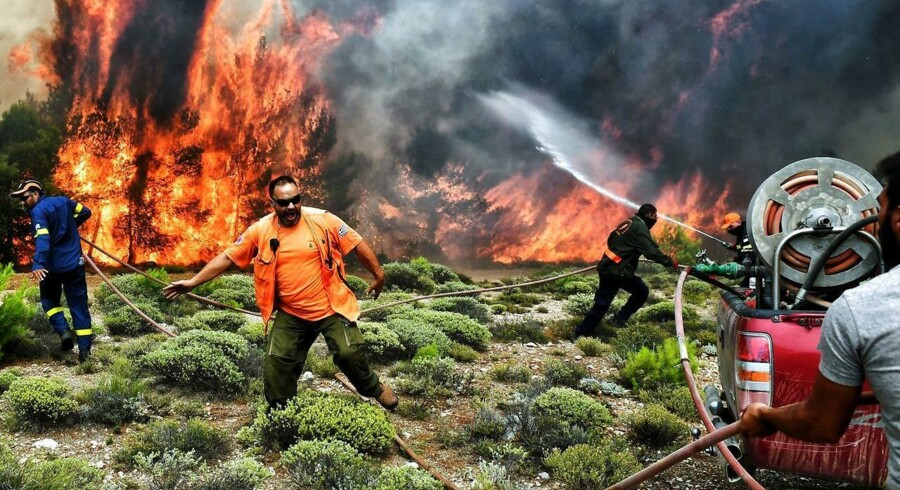 Brandfolk og frivillige kæmper mod flammerne fra en skovbrand ved byen Kineta. Skovbrandene i området omkrig Grækenlands hovedstad Athen har indtil videre kosten 79 mennesker livet, mindst 187 mennesker, herunder 23 børn, er kommet til skade, og antallet af savnede er fortsat uklart. / AFP PHOTO