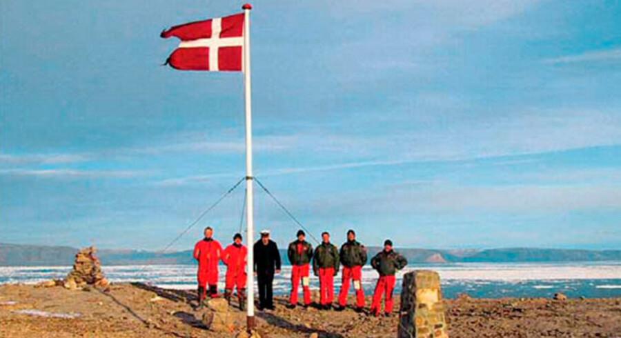 """En gruppe danske soldater stående ved siden af det danske flag på Hans Ø. Danmark og Canada har i flere år ligget i """"krig"""" om suveræniteten af den ubeboede ø, som mener at ligge i et område, der er rigt på olie og mineraler."""