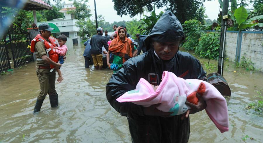 Redningsmandskab evakuerer lokale indbyggere fra de oversvømmede områder i den indiske delstat Kerala onsdag. Alle fly til den internationale lufthavn i Kochi er aflyst i tre dage på grund af vandmasserne. -/Ritzau Scanpix