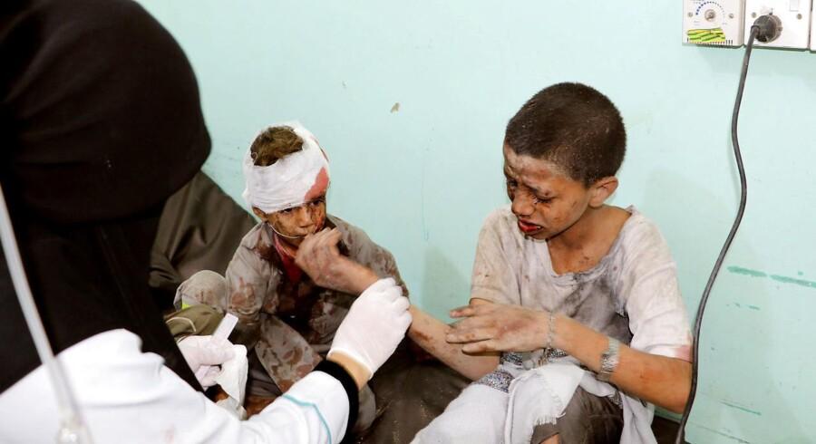 En doktor behandler sårede børn efter luftangrebet i Saada 9. august.