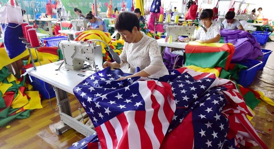 Arbejdere på fabrik i Kina syr amerikanske flag, alt imens de to store nationer rasler med toldsablerne. Foto/AFP Photo/Ritzau Scanpix.