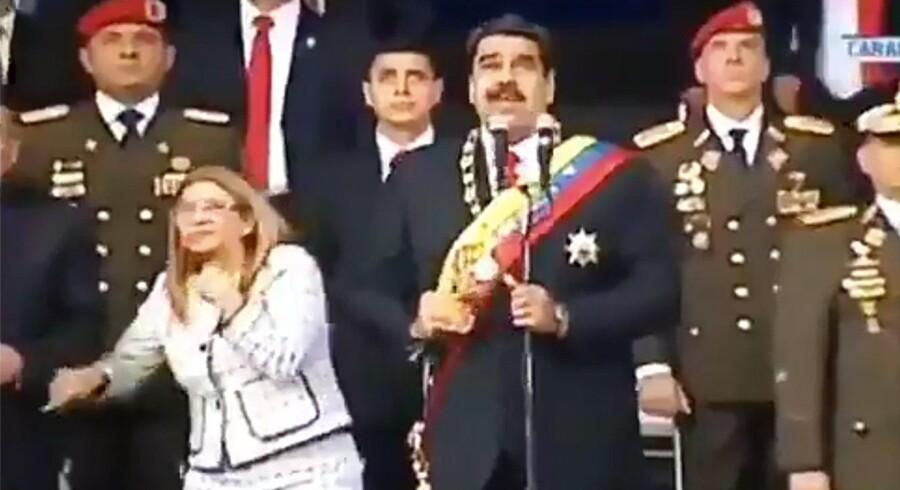 Et billede fra Venezuelan Television (VTV) viser præsident Nicolas Maduro (i midten), hans kone, Cilia Flores (t.v.), og flere højtstående officerer i det øjeblik, de hører en høj lyd under præsidentens tale sent lørdag eftermiddag lokal tid. Ho/Ritzau Scanpix