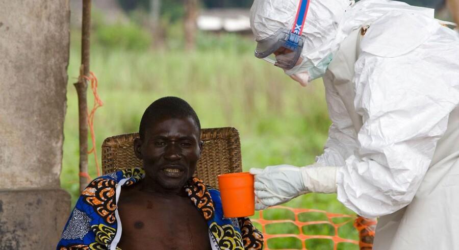ARKIVFOTO: En læge tilknyttet Læger uden Grænser giver vand til en patient smittet med ebola.