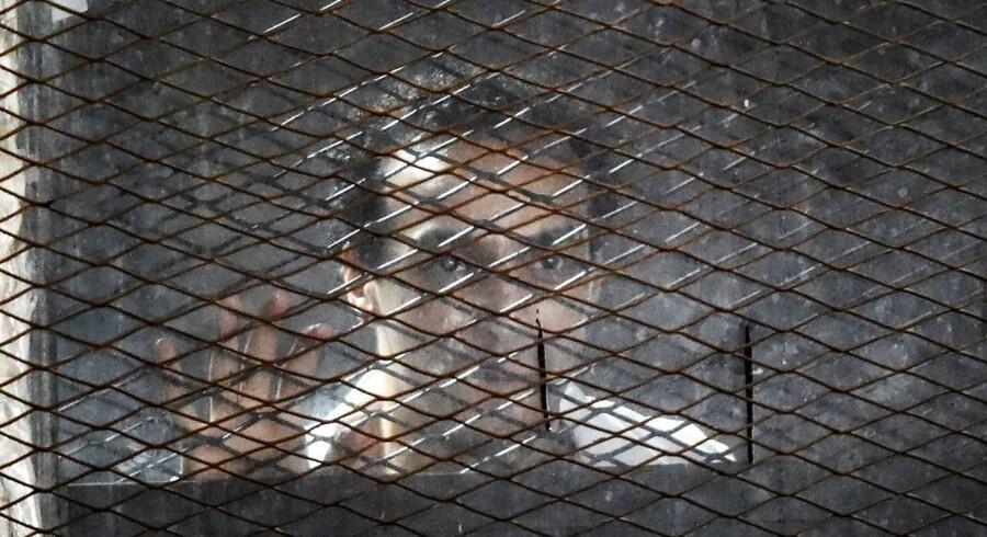 Den egyptiske fotojournalist Mahmoud Abu Zeid, der også er kendt under navnet Shawkan, bag tremmer under et tidligere retsmøde. Han er en af de anklagede i en masseretssag mod 739 mennesker, hvoraf de 75 fik en dødsdom lørdag. Amr Abdallah Dalsh/arkiv/Reuters