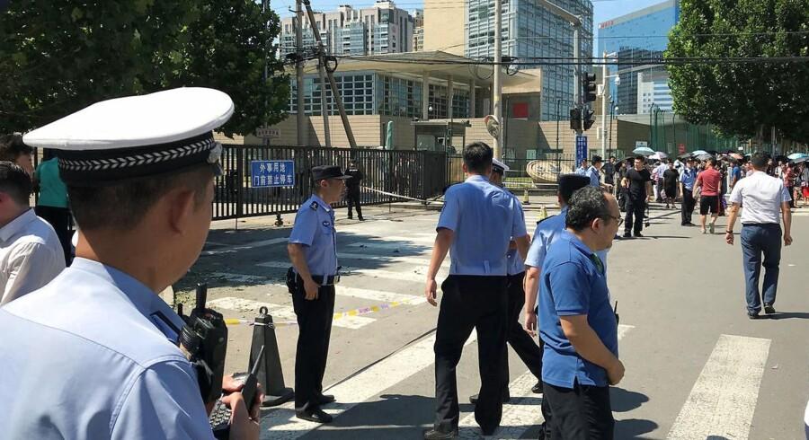 Poltitibetjente i Beijing står vagt ved den amerikanske ambassade i den kinesiske hovedstad, 26. juli 2018. REUTERS/Thomas Peter