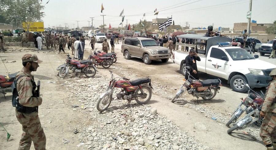 Sikkerhedsbetjente samler sig ved stedet for eksplosionen uden for et valgsted i byen Quetta. REUTERS/Naseer Ahmed
