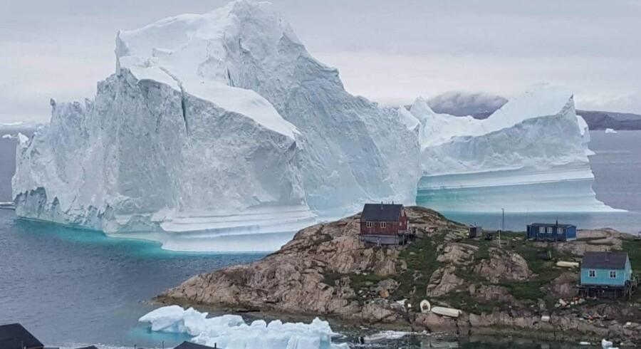Vejret kan måske betyde, at et stort isfjeld, der truer bygden Innaarsuit i Vestgrønland driver videre fredag aften. Men beboerne kan komme til at mangle mad og andre varer, da bygdens eneste butik ligger i det evakuerede område. Magnus Kristensen/Ritzau Scanpix